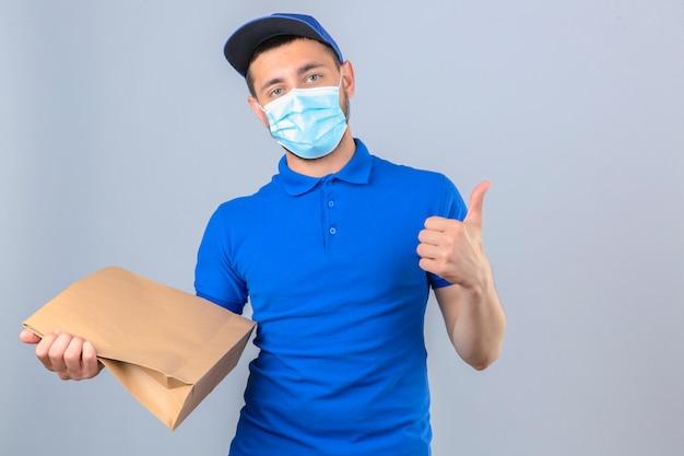 Junger lieferbote, der blaues poloshirt und kappe in der medizinischen schutzmaske steht, die mit papierpaket steht, das daumen oben über lokalisiertem weißem hintergrund zeigt