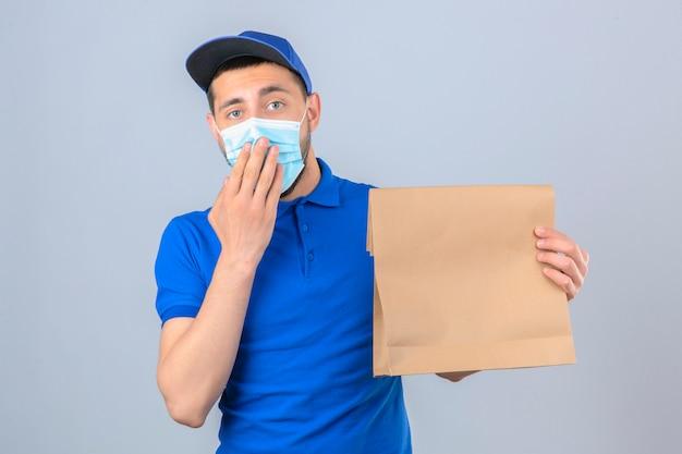 Junger lieferbote, der blaues poloshirt und kappe in der medizinischen schutzmaske steht, die mit papierpaket steht, das geschockten abdeckenden mund mit hand über lokalisiertem weißem hintergrund schaut