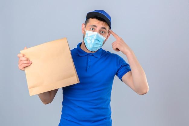 Junger lieferbote, der blaues poloshirt und kappe in der medizinischen schutzmaske trägt, die mit papierpaket steht, das auf kopf über lokalisiertem weißem hintergrund zeigt