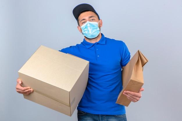 Junger lieferbote, der blaues poloshirt und kappe in der medizinischen schutzmaske trägt, die mit papierpaket und -box steht, die über lokalem weißem hintergrund sicher schauen