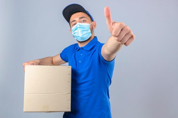 Junger lieferbote, der blaues poloshirt und kappe in der medizinischen schutzmaske trägt, die mit pappkarton steht, der daumen bis zur kamera über lokalisiertem weißem hintergrund zeigt