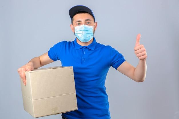 Junger lieferbote, der blaues poloshirt und kappe in der medizinischen schutzmaske trägt, die mit pappkarton steht, der sicheren blick des daumens über lokalisierten weißen hintergrund zeigt