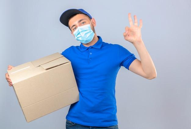 Junger lieferbote, der blaues poloshirt und kappe in der medizinischen schutzmaske trägt, die mit pappkarton steht und ok zeichen über lokalisiertem weißem hintergrund tut