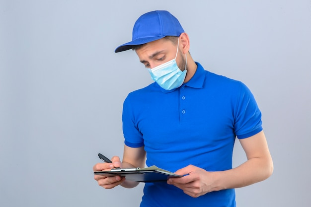 Junger lieferbote, der blaues poloshirt und kappe in der schützenden medizinischen maske steht, die mit zwischenablage schreiben, die über lokalisiertem weißem hintergrund schreibt