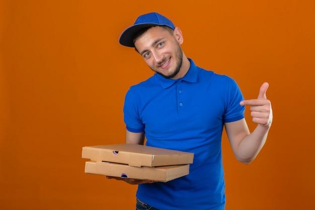 Junger lieferbote, der blaues poloshirt und kappe trägt, die mit stapel von pizzaschachteln stehen und kamera mit lächeln auf gesicht zeigen, das mit finger über lokalisiertem orangefarbenem hintergrund zeigt