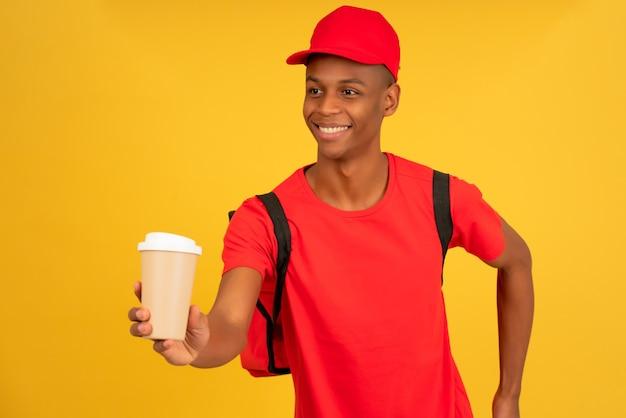 Junger lieferbote, der eine tasse kaffee zum mitnehmen hält.