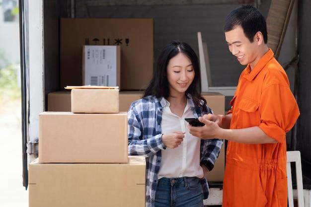 Junger lieferbote, der informationen über pakete zur frau zeigt