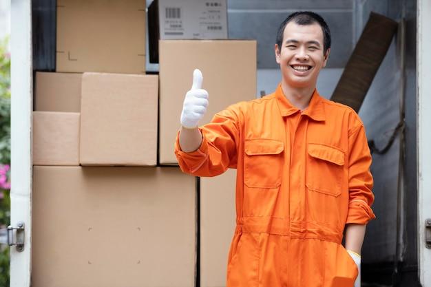 Junger lieferbote, der pakete im lieferwagen lädt