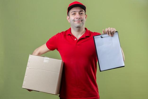 Junger lieferbote, der rote uniform hält, die pappkarton und zwischenablage mit rohlingen hält, die nach unterschrift fragen, die über lokalisiertem grünem hintergrund lächelt