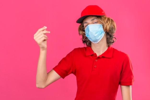Junger lieferbote, der rotes poloshirt und kappe in der medizinischen maske trägt, die eine geldgeste tut, die zuversichtlich über lokalisiertem rosa hintergrund schaut