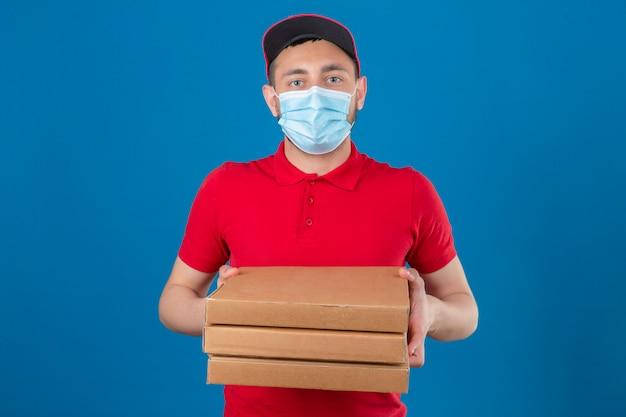 Junger lieferbote, der rotes poloshirt und kappe in der medizinischen schutzmaske trägt, die mit stapel von pizzakästen steht, die kamera mit ernstem gesicht über lokalisiertem blauem hintergrund betrachten