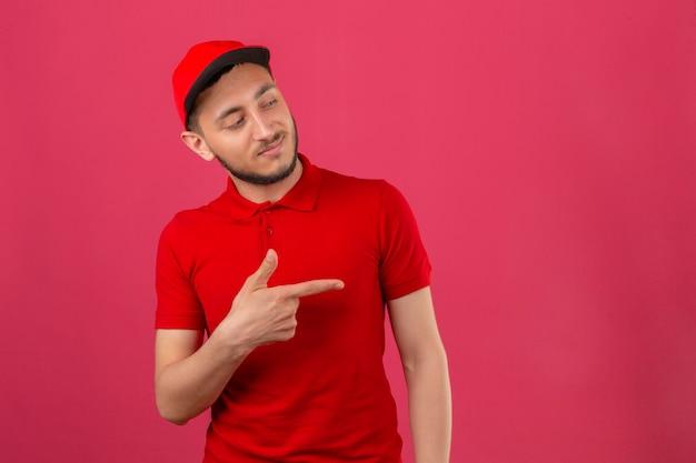 Junger lieferbote, der rotes poloshirt und kappe trägt, die zur seite zeigen, um etwas über lokalisiertem rosa hintergrund zu präsentieren