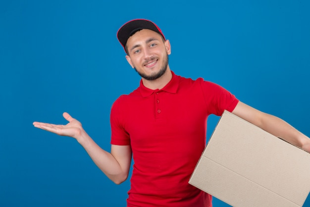 Junger lieferbote, der rotes poloshirt und mütze trägt, die mit der box steht, die fröhlich präsentiert und mit handfläche zeigt, die kamera über lokalisiertem blauem hintergrund betrachtet