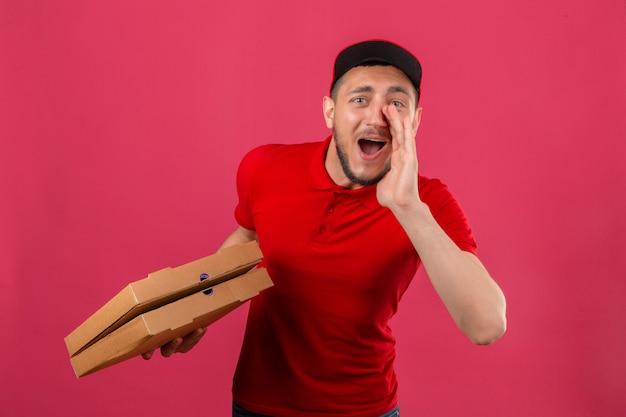 Junger lieferbote, der rotes poloshirt und mütze trägt, die mit pizzaschachteln stehen, die etwas mit hand nahe mund über lokalisiertem rosa hintergrund schreien und ankündigen