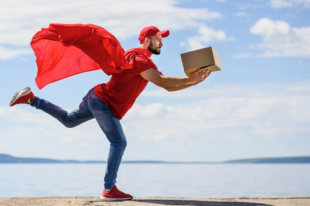 Junger lieferbote, der superheldenumhang trägt