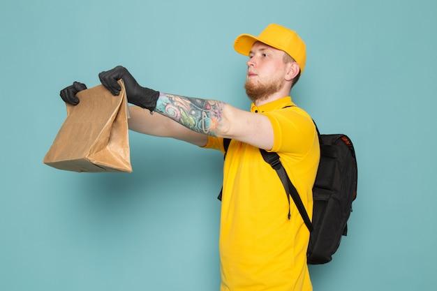 Junger lieferbote im gelben weißen jeansrucksack der gelben polo-kappe, der eine schachtel auf blau hält