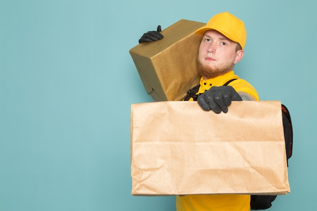 Junger lieferbote im gelben weißen rucksack der gelben polo-kappe, der kisten auf blau hält