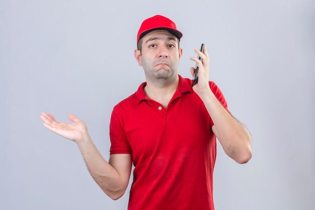Junger lieferbote im roten poloshirt und in der kappe, die ahnungslos und verwirrten ausdruck des mobiltelefons mit erhobenem arm sprechen, der zweifel über isoliertem weißem hintergrund hat