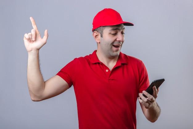 Junger lieferbote im roten poloshirt und in der kappe, die den bildschirm seines smartphones mit dem finger nach oben mit überraschtem blick betrachten, der fröhlich große idee über isoliertem weißem hintergrund lächelt
