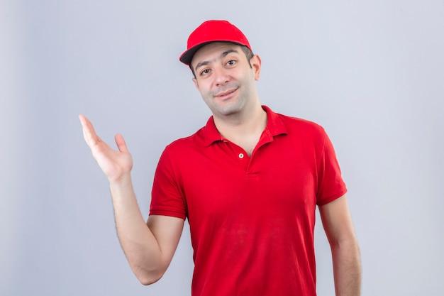 Junger lieferbote im roten poloshirt und in der kappe, die etwas mit hand über lokalisierten weißen hintergrund präsentieren
