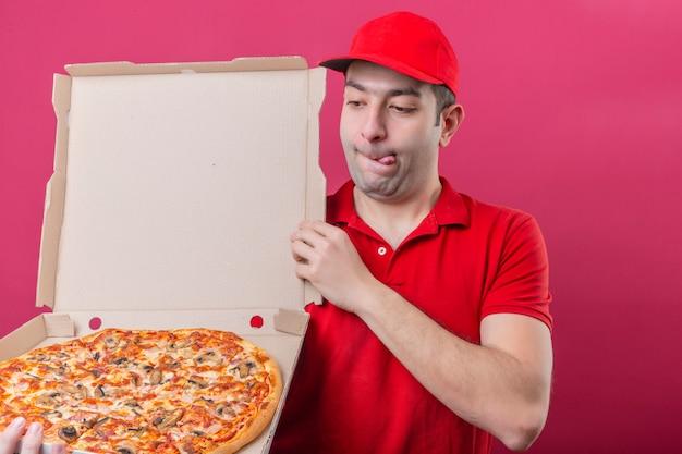 Junger lieferbote im roten poloshirt und in der kappe, die mit der schachtel der frischen pizza stehen, die es mit einem hungrigen lustvollen gesicht über lokalisiertem rosa hintergrund betrachtet