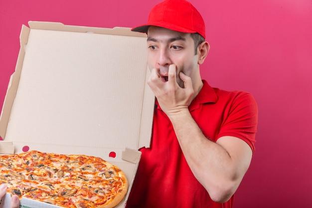 Junger lieferbote im roten poloshirt und in der kappe, die mit der schachtel der frischen pizza stehen, die es schockiert betrachtet, erschrocken über lokalisiertem rosa hintergrund