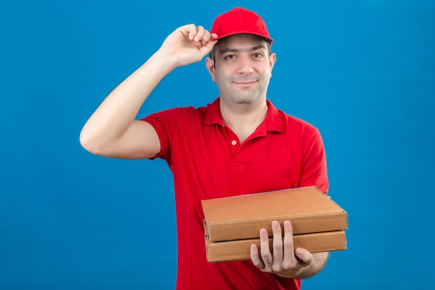 Junger lieferbote im roten poloshirt und in der kappe, die pizzaschachteln halten, die grußgeste machen, die sein selbstbewusstes lächeln der kappe auf gesicht über isolierter blauer wand berührt