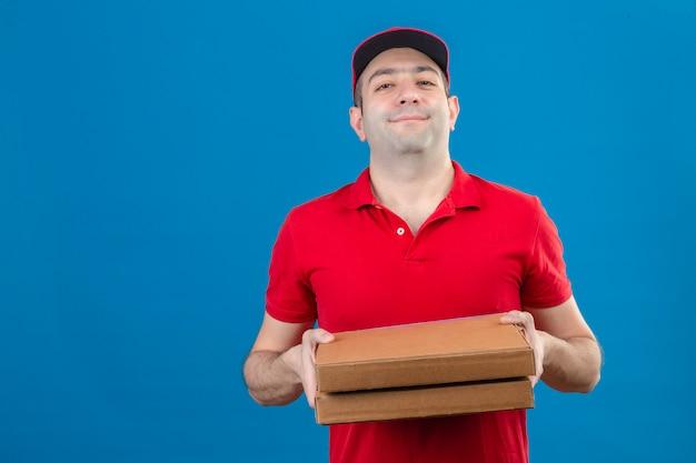 Junger lieferbote im roten poloshirt und in der kappe, die pizzaschachteln mit sicherem lächeln auf gesicht über isolierter blauer wand halten