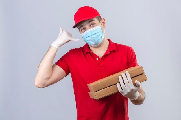 Junger lieferbote im roten poloshirt und in der kappe in der medizinischen maske, die pizzaschachteln hält, die mich geste nennen, die zuversichtlich über isolierte weiße wand schaut