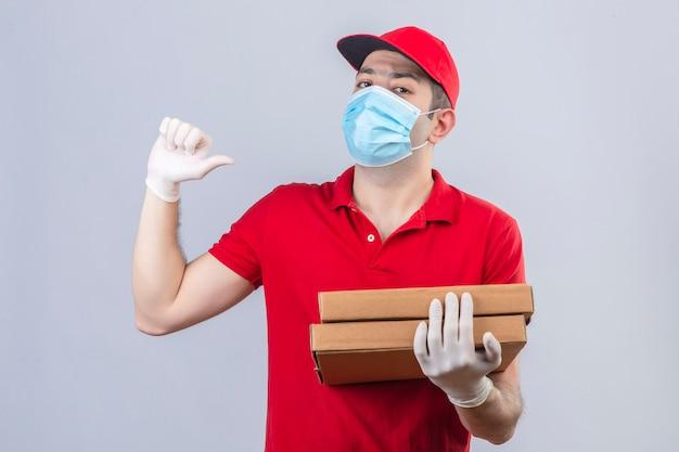 Junger lieferbote im roten poloshirt und in der kappe in der medizinischen maske, die pizzaschachteln hält, die zuversichtlich auf sich selbst über isolierte weiße wand zeigen