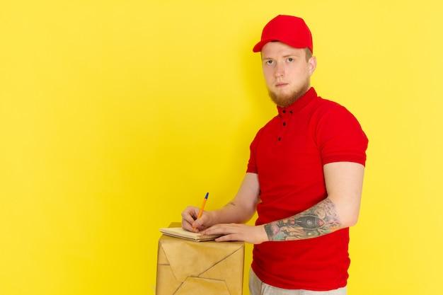 Junger lieferbote in den roten jeans der roten polo-roten kappe, die eine schachtel halten und auf gelb schreiben