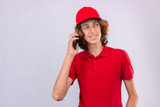 Junger lieferbote in der roten uniform, die auf handy spricht, das mit lächeln auf gesicht über lokalisiertem weißem hintergrund beiseite schaut
