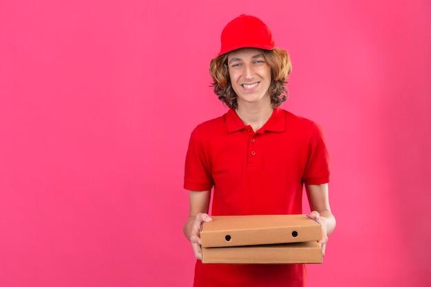 Junger lieferbote in der roten uniform, die pizzakästen hält, die fröhlich mit glücklichem gesicht über lokalisiertem rosa hintergrund lächeln