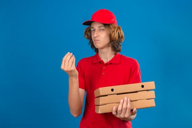 Junger lieferbote in der roten uniform, die pizzaschachteln hält, die köstliche geste mit der hand lächelnd über lokalisiertem blauem hintergrund machen