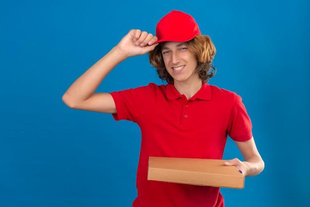 Junger lieferbote in der roten uniform, die pizzaschachteln hält, die seine kappe im grußlächeln freundlich über lokalisierten blauen hintergrund berühren