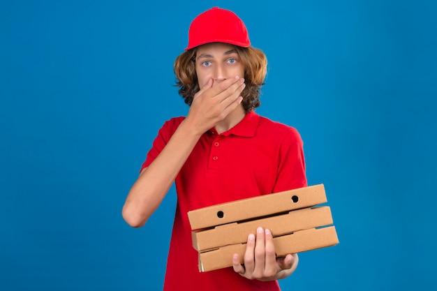 Junger lieferbote in der roten uniform, die pizzaschachteln hält, die überrascht mund mit hand über lokalisierten blauen hintergrund bedeckend suchen