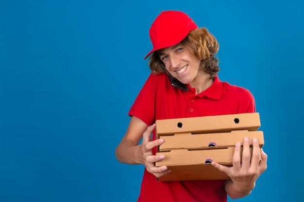 Junger lieferbote in der roten uniform, die pizzaschachteln hält, während auf mobiltelefon lächelnd mit glücklichem gesicht über lokalisiertem blauem hintergrund spricht
