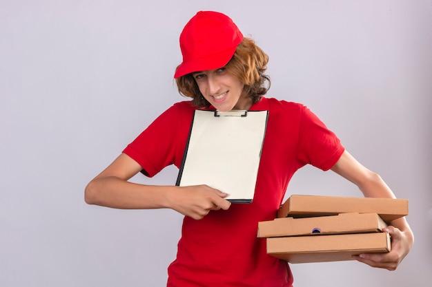 Junger lieferbote in der roten uniform, die pizzaschachteln und zwischenablage hält und um unterschrift auf leerzeichen über lokalisiertem weißem hintergrund bittet