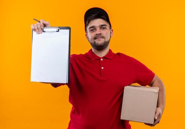 Junger lieferbote in der roten uniform und im kappenhaltekastenpaket, das zwischenablage mit leeren seiten zeigt, die um unterschrift bitten