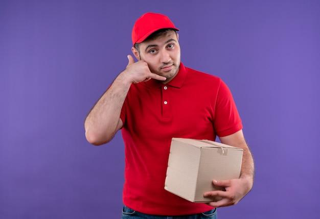 Junger lieferbote in der roten uniform und in der kappe, die box-paket macht, ruft mich geste lächelnd an, die zuversichtlich steht, über lila wand zu stehen
