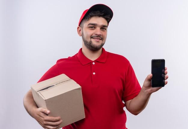 Junger lieferbote in der roten uniform und in der kappe, die box-paket zeigt smartphone, das kamera mit selbstbewusstem lächeln betrachtet