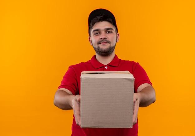 Junger lieferbote in der roten uniform und in der kappe, die boxpaket hält, das zuversichtlich lächelt