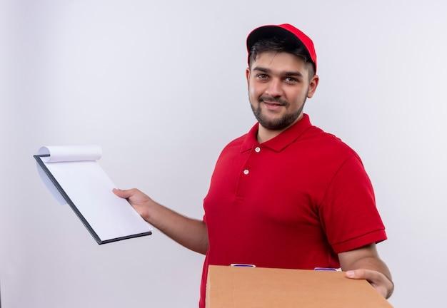 Junger lieferbote in der roten uniform und in der kappe, die boxpaket und zwischenablage mit leeren seiten hält, die um unterschrift bitten