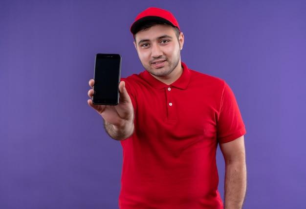 Junger lieferbote in der roten uniform und in der kappe, die das lächelnde smartphone zeigt, das zuversichtlich über lila wand steht