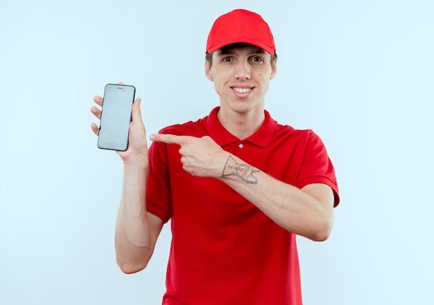Junger lieferbote in der roten uniform und in der kappe, die das smartphone zeigt, das mit dem finger auf es schaut, das zuversichtlich steht, über weißer wand zu stehen