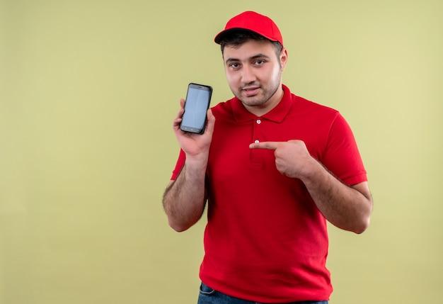 Junger lieferbote in der roten uniform und in der kappe, die das smartphone zeigt, das mit dem finger darauf zeigt und zuversichtlich steht, über grüner wand zu stehen