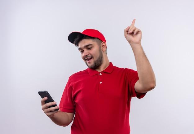Junger lieferbote in der roten uniform und in der kappe, die den bildschirm seines smartphones betrachten, der mit dem finger oben zeigt große idee hat