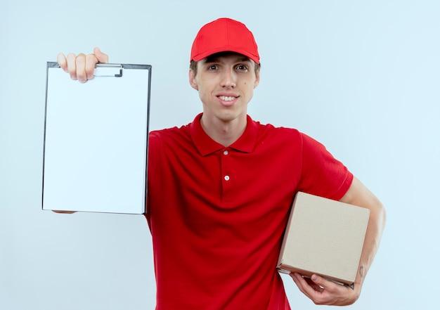 Junger lieferbote in der roten uniform und in der kappe, die den pappkarton hält, der zwischenablage zeigt, die nach unterschriftenlächeln über weißer wand fragt
