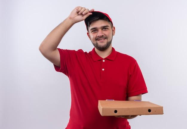 Junger lieferbote in der roten uniform und in der kappe, die die piza-box hält, die kamera betrachtet, die zuversichtlich seine kappe berührt