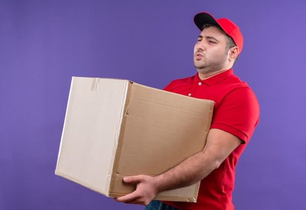 Junger lieferbote in der roten uniform und in der kappe, die großen pappkarton hält, der unwohl leidet, das unter schwerem gewicht steht, das über lila wand steht
